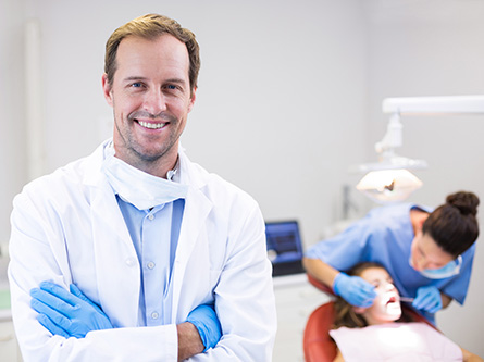 Portrait,Of,Dentist,Standing,With,Arms,Crossed,In,Clinic